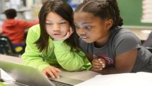 Two children sharing a Chromebook.