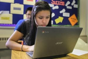 Girl using Chromebook in the classroom.