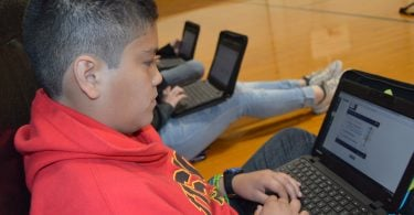 Students engaged with Chromebooks and Canvas