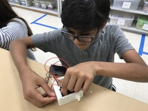 Student wiring flashlight while building global connections