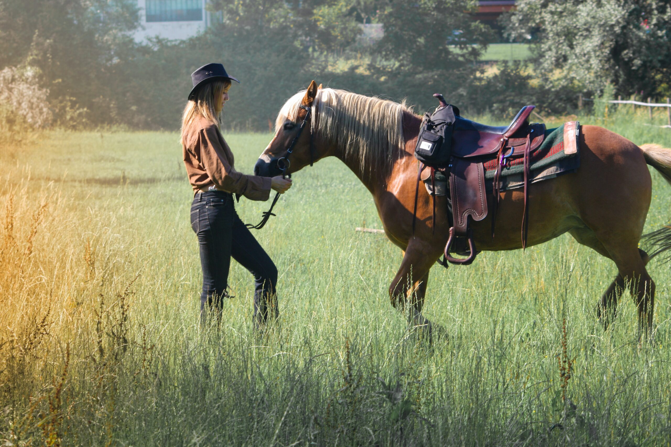 a young woman stands in a field with a saddled horse
